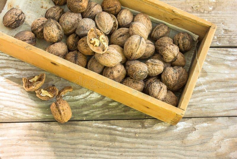 Πυρήνες ξύλων καρυδιάς και ολόκληρα ξύλα καρυδιάς στον αγροτικό παλαιό ξύλινο πίνακα στοκ φωτογραφία με δικαίωμα ελεύθερης χρήσης