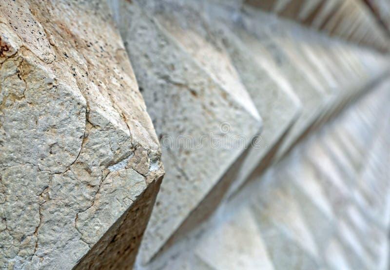 Πυραμίδα-διαμορφωμένο υπόβαθρο πετρών στον τοίχο συνόρων της κατασκευής στοκ εικόνες με δικαίωμα ελεύθερης χρήσης