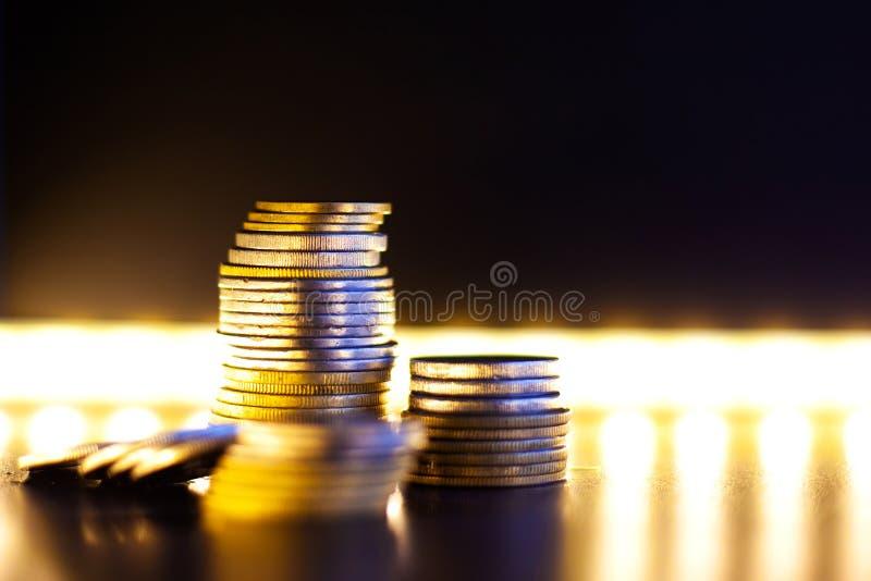 Πυραμίδα των ασημένιων και χρυσών νομισμάτων με τη θερμή έννοια πυραμίδων φωτισμού οικονομική στοκ εικόνες