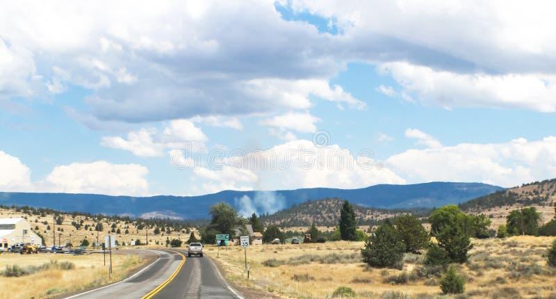 Πυρκαγιά στην απόσταση σε βόρεια Καλιφόρνια - που στο δρόμο 2 παρόδων κοντά σε Susansville με τα βουνά και τον καπνό στην απόστασ στοκ εικόνες