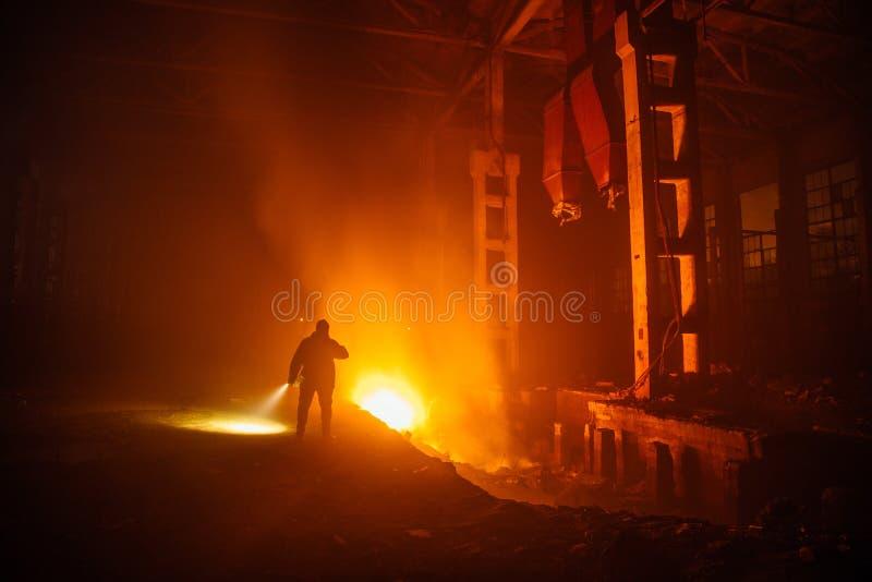 Πυρκαγιά στο εργοστάσιο Οι πυροσβέστες εξετάζουν τις συνέπειες της πυρκαγιάς Ανθρώπινη σκιαγραφία στο υπόβαθρο πυρκαγιάς στοκ φωτογραφία με δικαίωμα ελεύθερης χρήσης