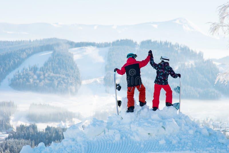 Πυροβοληθείς ενός ζεύγους υψηλού fiving ο ένας τον άλλον που θέτει πάνω από ένα χιονώδες βουνό που παρατηρεί τη ζαλίζοντας χειμερ στοκ εικόνες