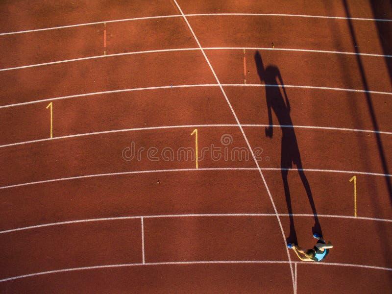 Πυροβοληθείς ενός νέου αρσενικού αθλητή που εκπαιδεύει σε μια διαδρομή αγώνων στοκ εικόνες