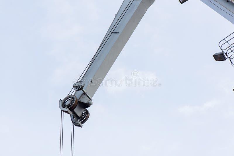 Πυροβοληθείς ενός παλαιού, σκουριασμένου γερανού λιμένων που προετοιμάζεται να ανυψώσει το φορτίο στο σκάφος στο συννεφιάζω υπόβα στοκ εικόνες