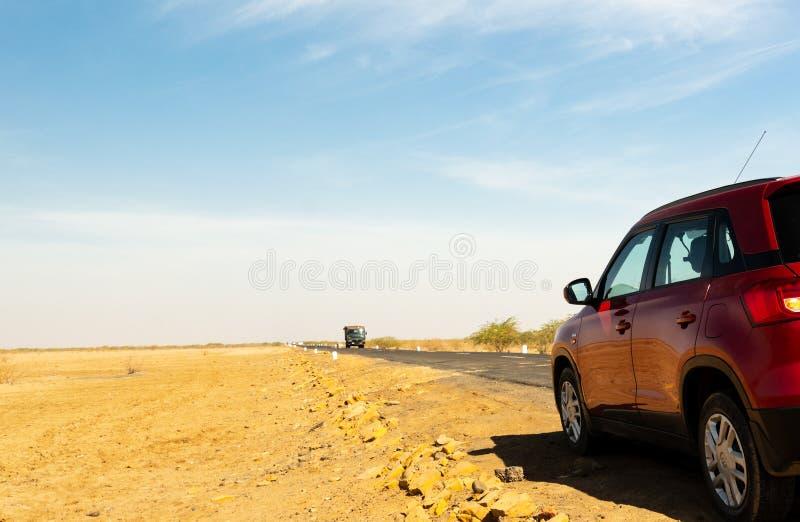 Πυροβοληθείς παρουσιάζοντας κόκκινο αυτοκίνητο σε ένα μακροχρόνιο τέντωμα της κενής εθνικής οδού σε Rann Kutch Gujarat στοκ φωτογραφία με δικαίωμα ελεύθερης χρήσης