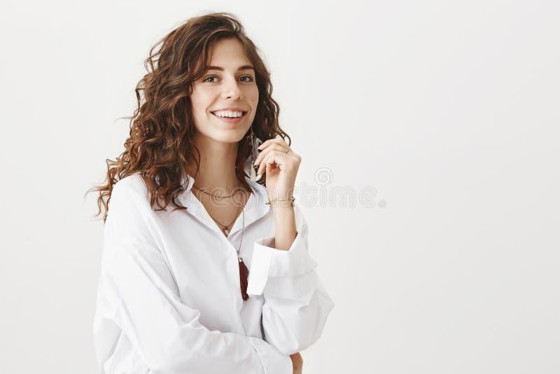 Πυροβοληθείς της θετικής ελκυστικής επιτυχούς γυναίκας μπλούζα, στάση μισό-που γυρίζουν στην άσπρη πέρα από το γκρίζο υπόβαθρο με στοκ εικόνα