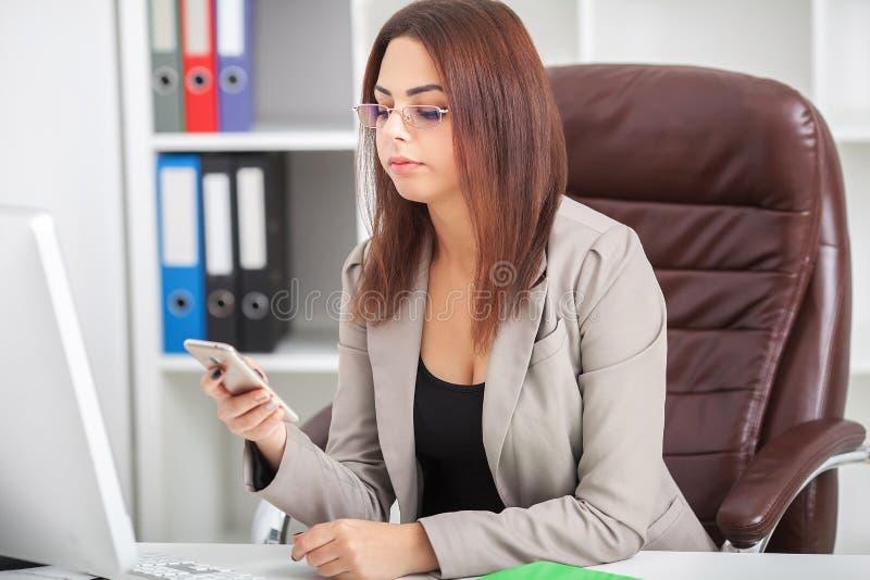 Πυροβοληθείς της όμορφης νέας συνεδρίασης γυναικών στη μετάβαση thr γραφείων εργασίας της στοκ εικόνα