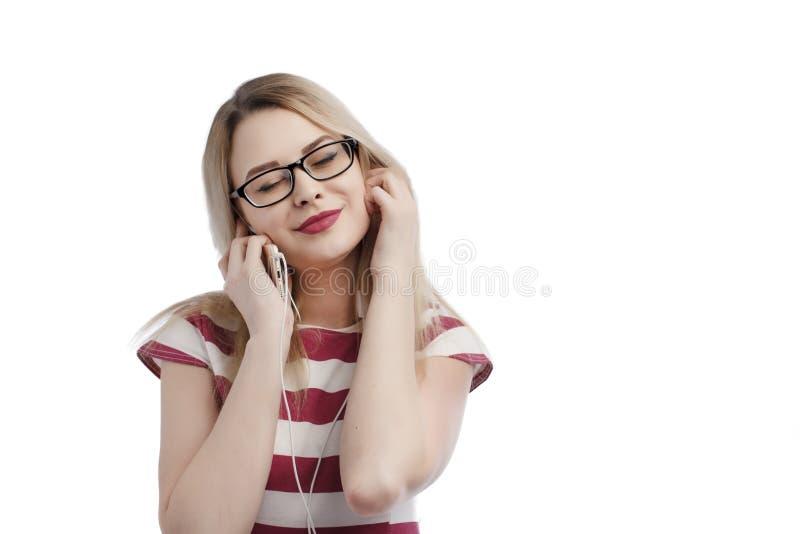 Πυροβοληθείς του όμορφου αστικού καυκάσιου κοριτσιού με τα ξανθά μαλλιά που κρατά το καθιερώνον τη μόδα smartphone, μουσική ακούσ στοκ φωτογραφία με δικαίωμα ελεύθερης χρήσης