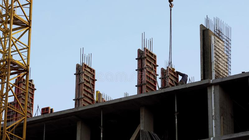 Πυροβοληθε'ντες εργοτάξιο εργαζόμενοι που εγκαθιστούν την ασφάλεια κατασκευής κατοικίας συμπαγών τοίχων στοκ φωτογραφία με δικαίωμα ελεύθερης χρήσης