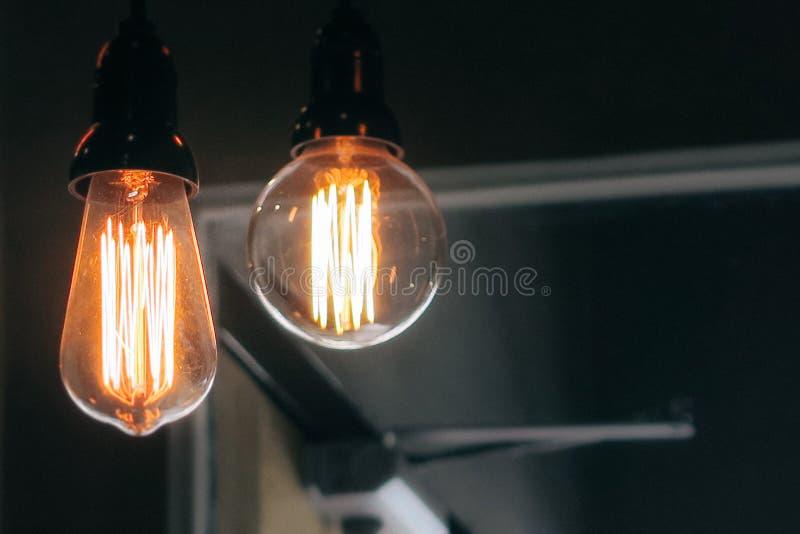 Πυροβολισμός κινηματογραφήσεων σε πρώτο πλάνο δύο αναμμένων μεγάλων lightbulbs σε ένα σκοτεινό υπόβαθρο στοκ φωτογραφία