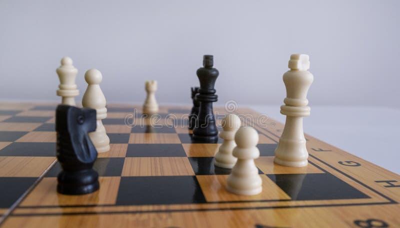 Πυροβολισμός κινηματογραφήσεων σε πρώτο πλάνο των ειδωλίων σκακιού σε μια σκακιέρα με ένα θολωμένο άσπρο υπόβαθρο στοκ εικόνες