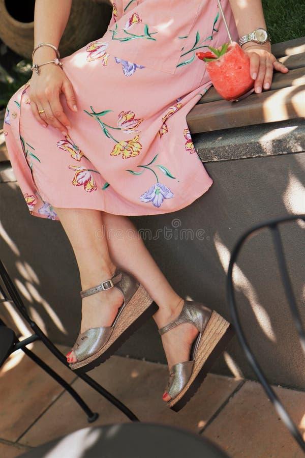 Πυροβολισμός κινηματογραφήσεων σε πρώτο πλάνο των κομψών ποδιών ενός θηλυκού που φορά ένα φόρεμα με έναν χυμό φραουλών στην πλευρ στοκ φωτογραφία
