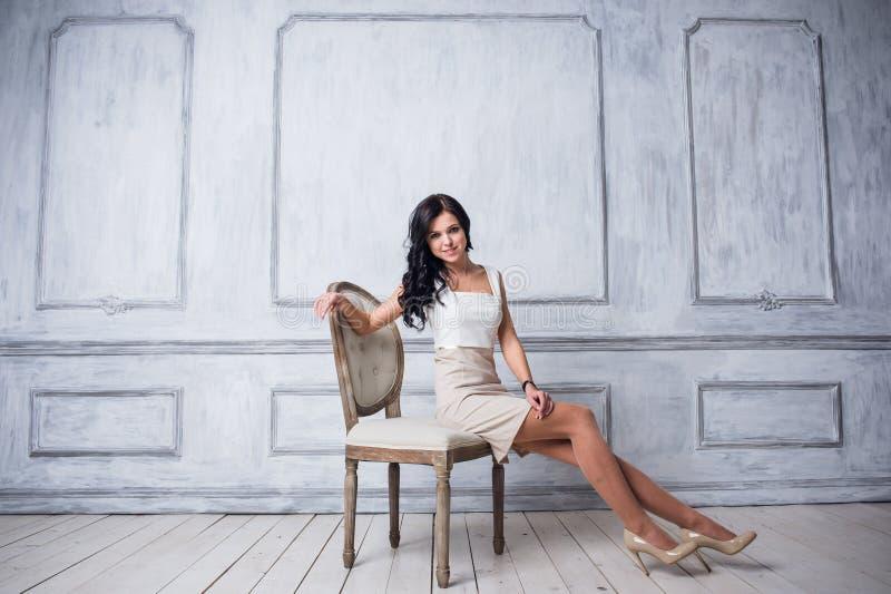 Πυροβολισμός μόδας της νέας όμορφης γυναίκας στην άσπρη σύντομη συνεδρίαση φορεμάτων στην παλαιά καρέκλα στοκ φωτογραφία με δικαίωμα ελεύθερης χρήσης