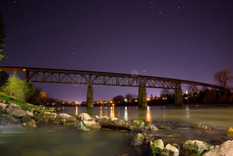 Πυροβολισμός νύχτας του τρίποδου τραίνων πέρα από τον ποταμό του Σακραμέντο σε Redding, ασβέστιο στοκ εικόνα με δικαίωμα ελεύθερης χρήσης