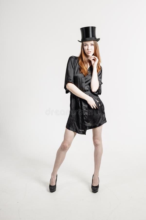 Πυροβολισμός στούντιο μιας νέας γυναίκας σε ένα μαύρα φόρεμα και ένα καπέλο στοκ φωτογραφίες