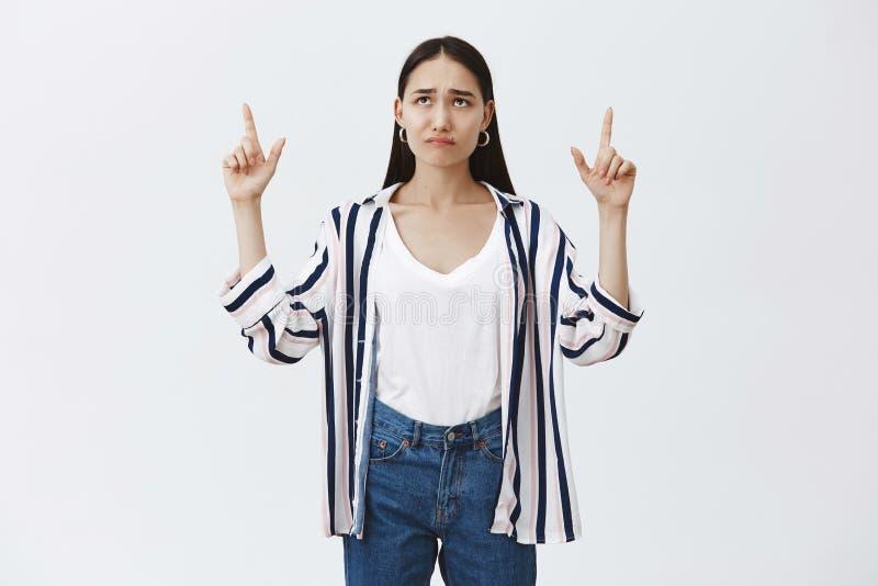 Πυροβολισμός στούντιο της και θλιβερής χαριτωμένης γυναίκας με τη σκοτεινή τρίχα στη ριγωτή μπλούζα, που και που δείχνοντας και στοκ εικόνα με δικαίωμα ελεύθερης χρήσης