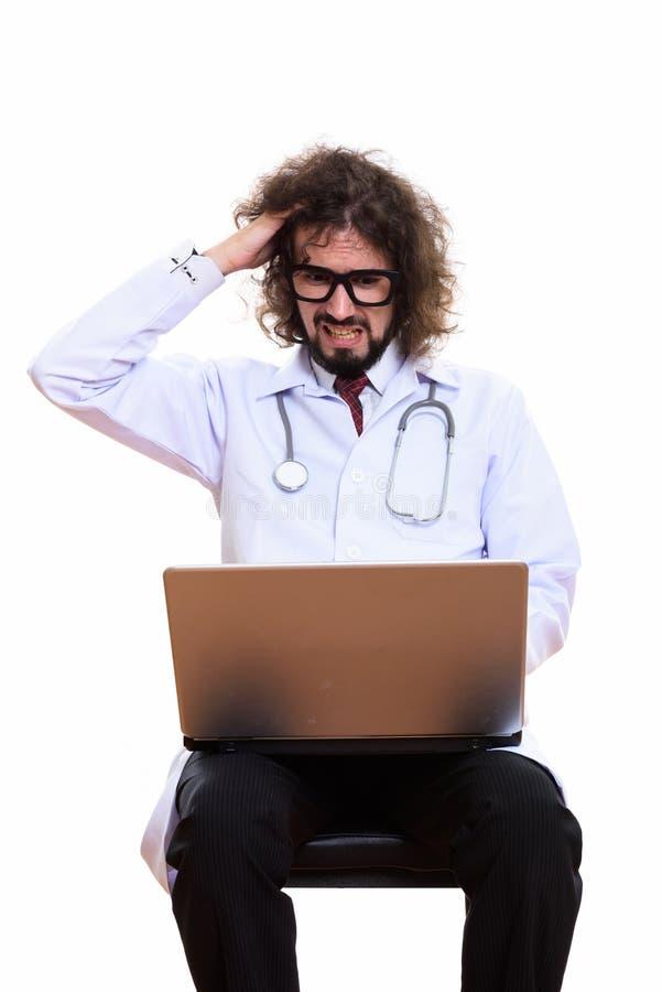 Πυροβολισμός στούντιο του τονισμένου γιατρού ατόμων που χρησιμοποιεί το lap-top με το χέρι σε δικοί του στοκ εικόνα