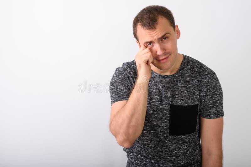 Πυροβολισμός στούντιο του τονισμένου νέου μυϊκού ατόμου που φαίνεται λυπημένου ενώ κραυγή στοκ εικόνες