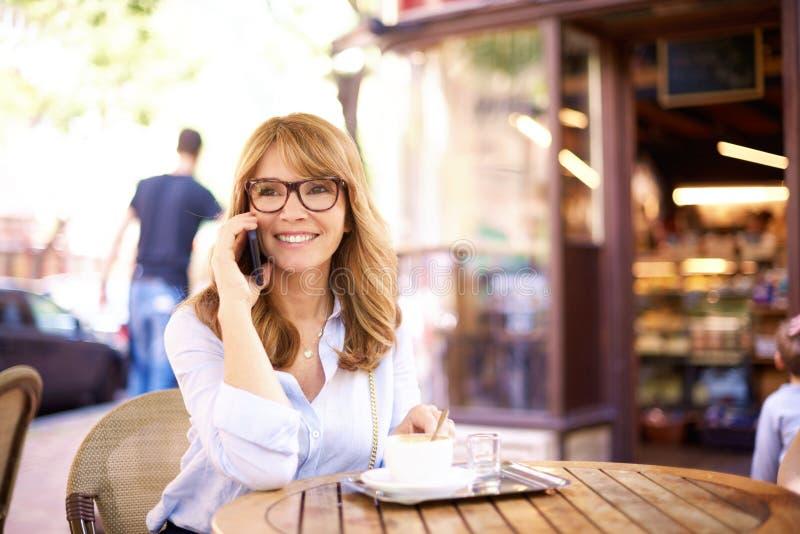 Πυροβολισμός της μέσης ηλικίας συνεδρίασης γυναικών στη καφετερία και της παραγωγής μιας κλήσης στοκ εικόνες