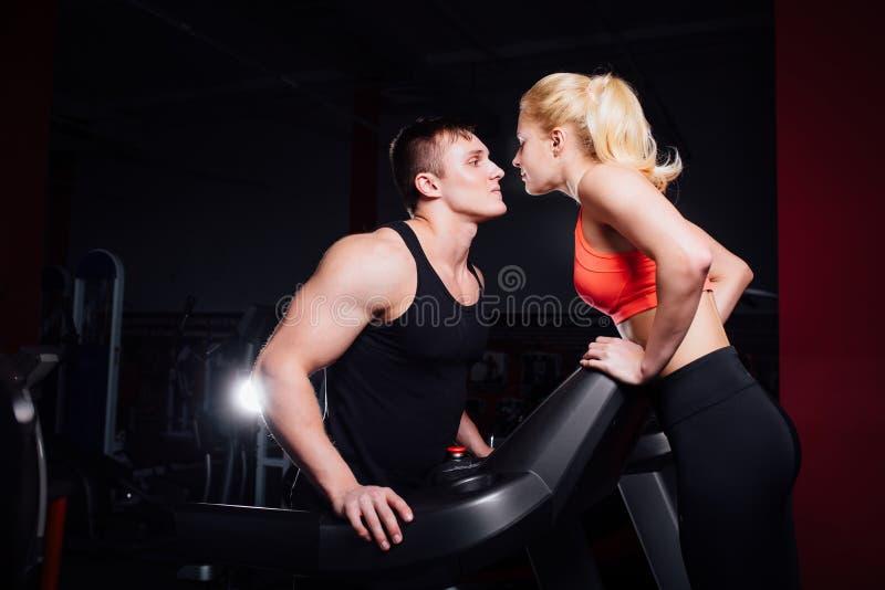 Πυροβοληθείς ενός χαριτωμένου ζεύγους που φιλά το ένα το άλλο κάνοντας την άσκηση στη γυμναστική treadmill στοκ εικόνες