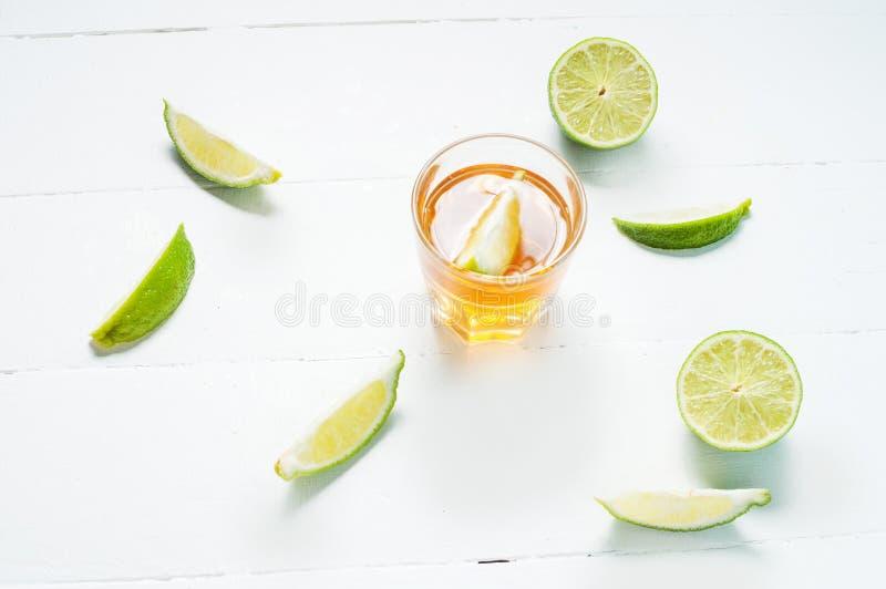 Πυροβολισμοί του χρυσού tequila με τις φέτες ασβέστη και του άλατος στο άσπρο ξύλινο BA στοκ φωτογραφίες με δικαίωμα ελεύθερης χρήσης