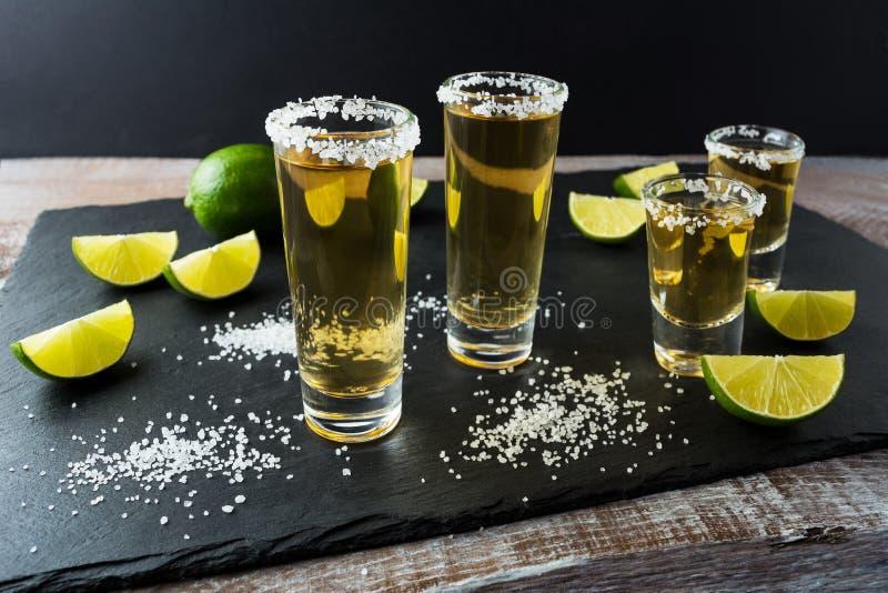Πυροβολισμοί Tequila με τον ασβέστη στο μαύρο υπόβαθρο πετρών στοκ φωτογραφία