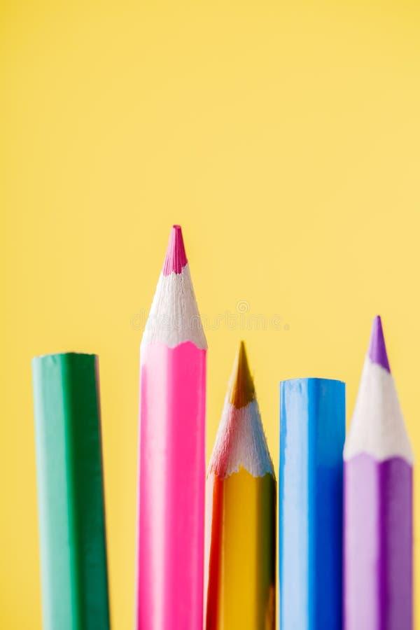 Πυροβολισμός κινηματογραφήσεων σε πρώτο πλάνο των χρωματισμένων μολυβιών που στέκονται στο κίτρινο υπόβαθρο στοκ φωτογραφία με δικαίωμα ελεύθερης χρήσης