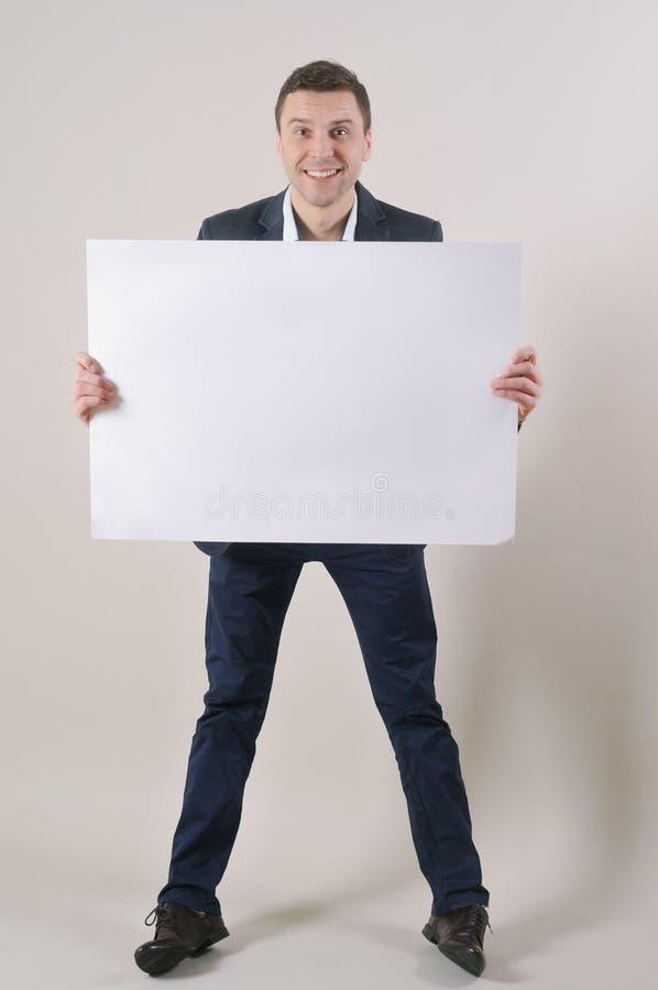 Πυροβολισμός στούντιο ενός όμορφου ατόμου σε ένα κοστούμι που κρατά ψηλά ένα κενό φύλλο στοκ εικόνες
