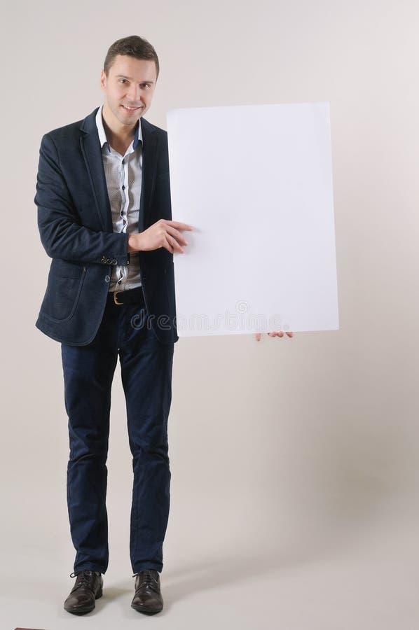 Πυροβολισμός στούντιο ενός όμορφου ατόμου σε ένα κοστούμι που κρατά ψηλά ένα κενό λευκό στοκ φωτογραφία με δικαίωμα ελεύθερης χρήσης