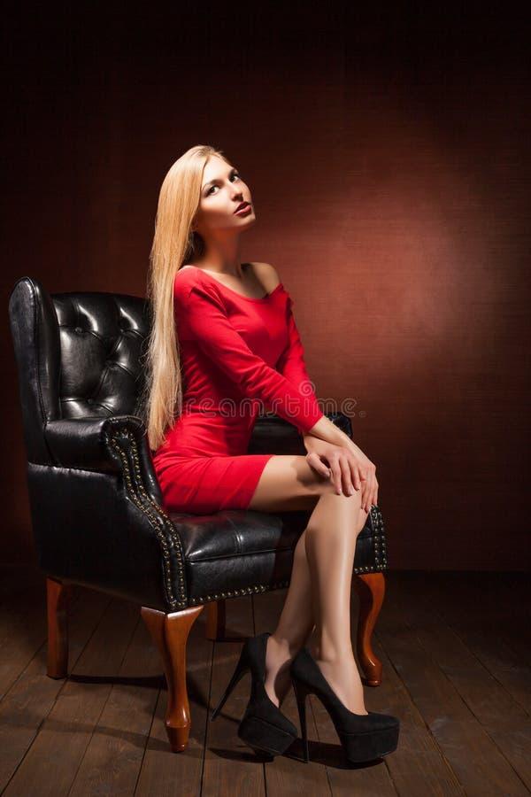 Πυροβολισμός της όμορφης γυναίκας που φορά την κόκκινη συνεδρίαση φορεμάτων στοκ εικόνα με δικαίωμα ελεύθερης χρήσης