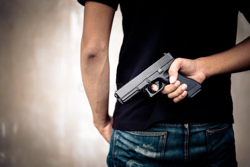 Πυροβόλο όπλο δορών ληστών στην πλάτη του Εγκληματίας και έννοια δολοφονίας Διαγώνια επεξεργασία και διασπασμένος τόνος πιό pinte στοκ εικόνες