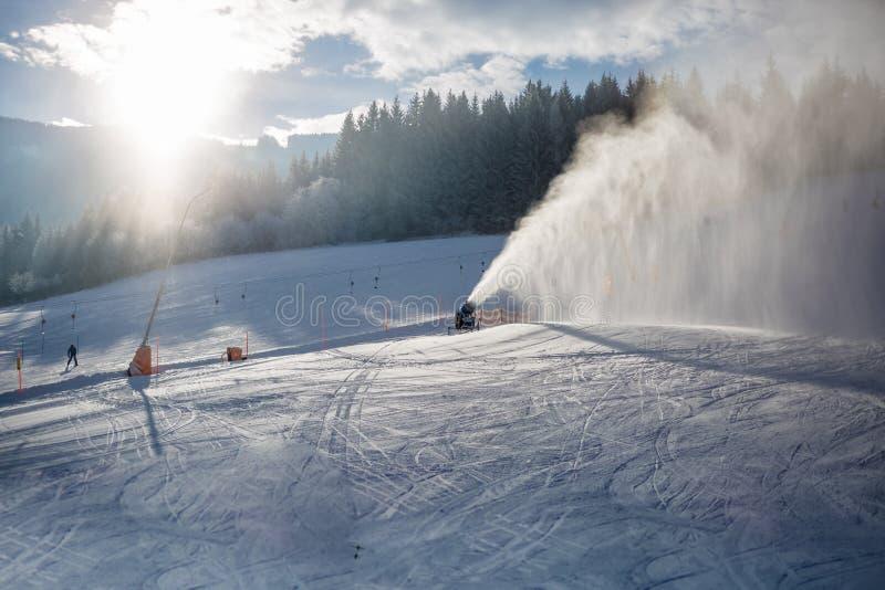 Πυροβόλα χιονιού που λειτουργούν στην κλίση σκι στις Άλπεις στην ηλιόλουστη ημέρα στοκ φωτογραφία με δικαίωμα ελεύθερης χρήσης