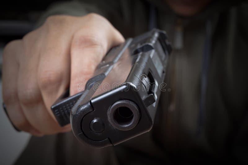 Πυροβόλο όπλο διαθέσιμο και που δείχνει με το δολοφόνο, την ασφάλεια και το εγκληματικό concep στοκ εικόνες