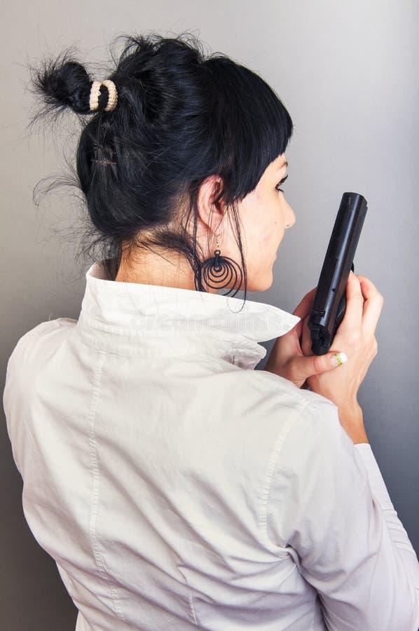 Πυροβόλο όπλο κοριτσιών Brunette holdinh στοκ εικόνες
