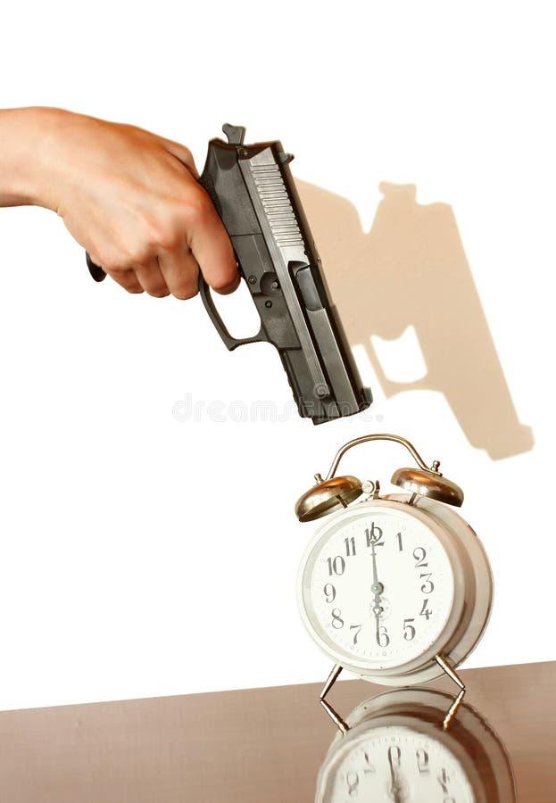 Πυροβόλο όπλο πιστολιών που δείχνει σε ένα ξυπνητήρι στοκ εικόνες