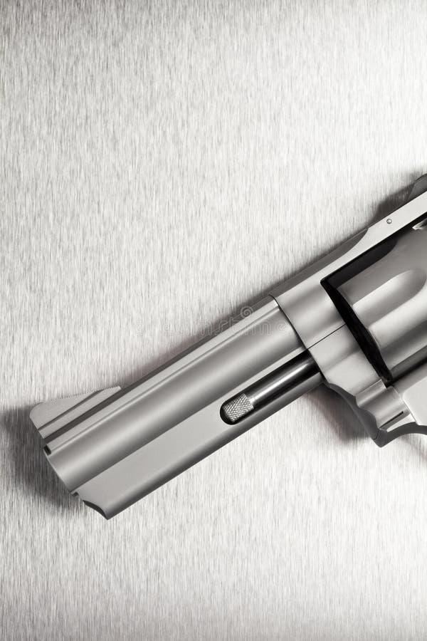 Πυροβόλο όπλο στο βουρτσισμένο υπόβαθρο μετάλλων στοκ φωτογραφία