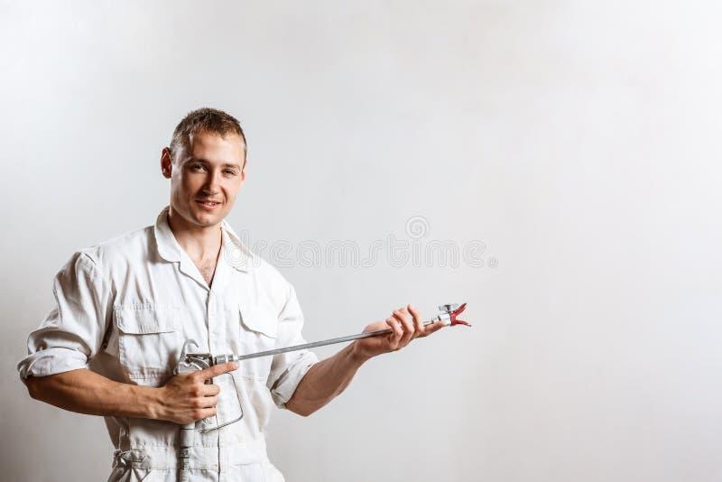 Πυροβόλο όπλο ψεκασμού εκμετάλλευσης εργαζομένων πέρα από τον άσπρο τοίχο διάστημα αντιγράφων στοκ εικόνα