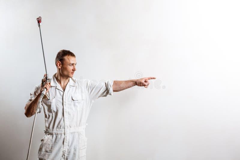 Πυροβόλο όπλο ψεκασμού εκμετάλλευσης εργαζομένων πέρα από τον άσπρο τοίχο διάστημα αντιγράφων στοκ φωτογραφία με δικαίωμα ελεύθερης χρήσης