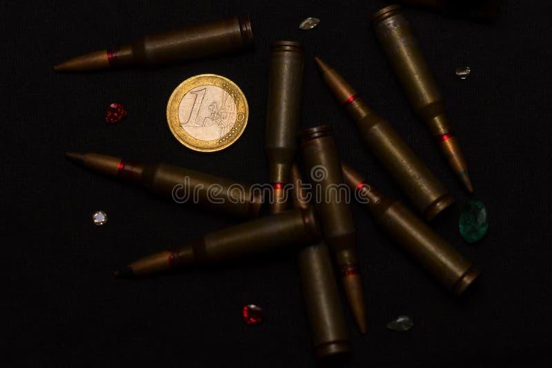 Πυρομαχικά τουφεκιών γύρω από πολύτιμους λίθους ενός τους ευρο- νομίσματος wigh στο μαύρο υπόβαθρο Συμβολίζει τον πόλεμο για τα χ στοκ εικόνες με δικαίωμα ελεύθερης χρήσης