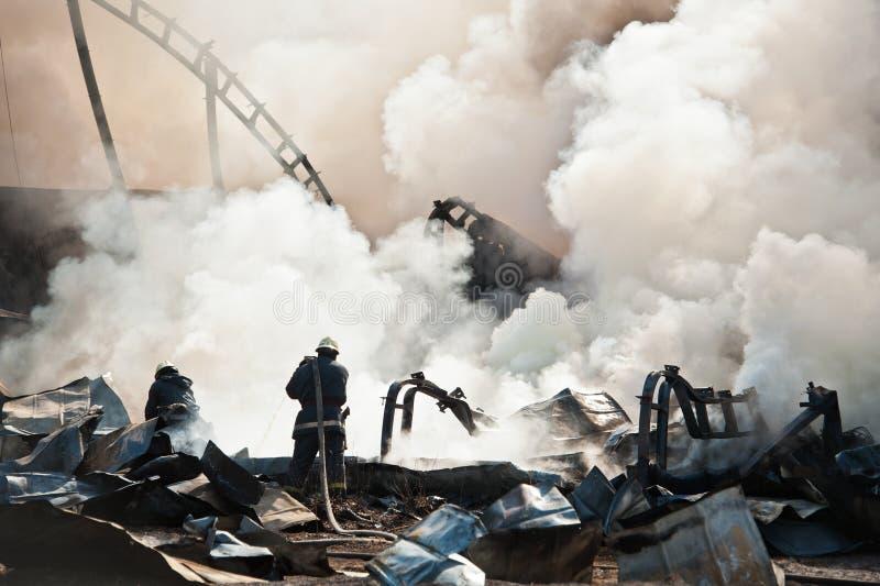 Πυροσβέστες που εξαφανίζουν την πυρκαγιά στοκ εικόνα
