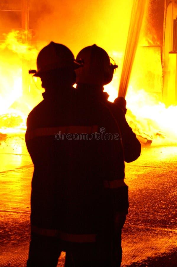 Πυροσβέστες που παλεύουν τη μεγάλη φλόγα στοκ εικόνα με δικαίωμα ελεύθερης χρήσης