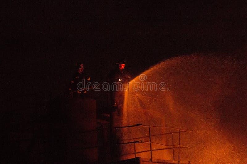 Πυροσβέστες σε έναν σωρό με τη μάνικα στοκ εικόνες με δικαίωμα ελεύθερης χρήσης