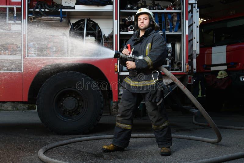 Πυροσβέστης με τη μάνικα νερού κοντά στο φορτηγό στοκ εικόνες