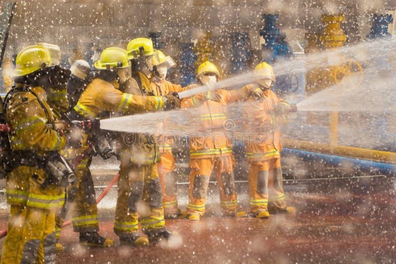 Πυροσβέστης που επιδεικνύει πώς να χρησιμοποιήσει τους ψεκαστήρες μιας πυρκαγιάς σε μια πυρκαγιά κατάρτισης στοκ φωτογραφία με δικαίωμα ελεύθερης χρήσης