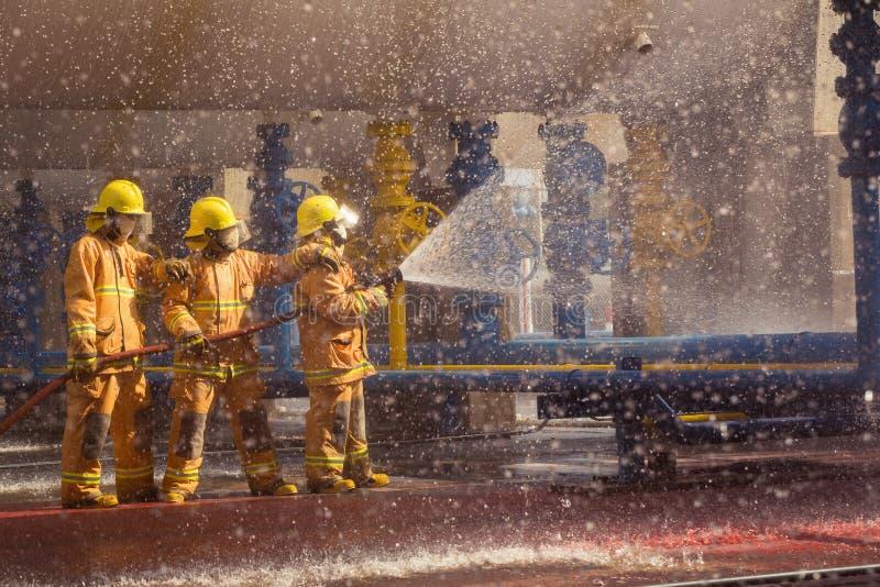 Πυροσβέστης που επιδεικνύει πώς να χρησιμοποιήσει τους ψεκαστήρες μιας πυρκαγιάς σε μια πυρκαγιά κατάρτισης στοκ εικόνες