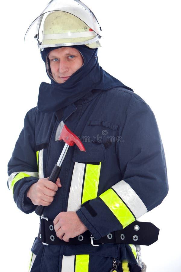 Πυροσβέστης που κρατά ένα κόκκινο τσεκούρι πυρκαγιάς στοκ εικόνες