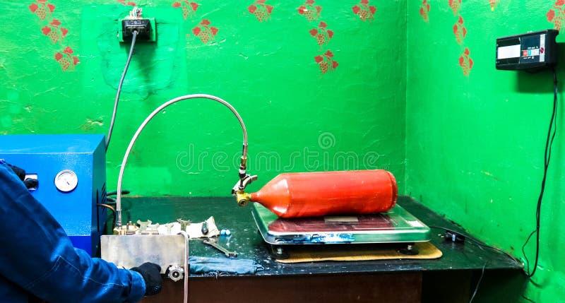 Πυροσβεστήρας με κόκκινο διοξείδιο του άνθρακα, ο κύλινδρος βρίσκεται στις κλίμακες για ποιοτικό έλεγχο Σταθμός φόρτισης πυροσβεσ στοκ εικόνες
