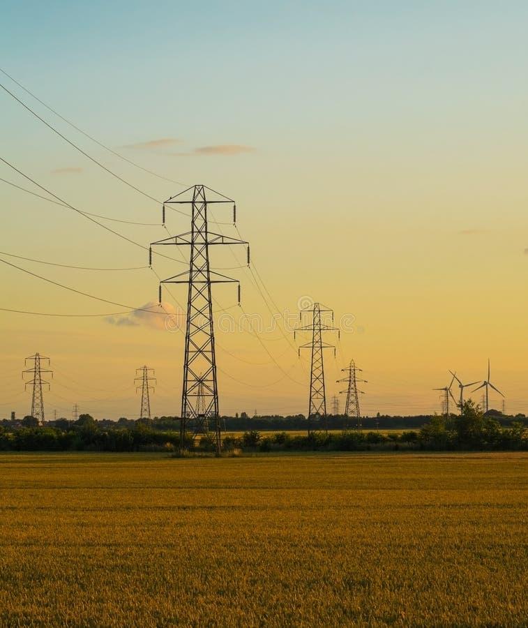 Πυλώνες ηλεκτρικής ενέργειας στο πεδίο κριθαριού στοκ εικόνες με δικαίωμα ελεύθερης χρήσης