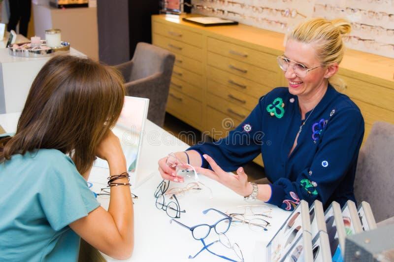 Πωλήτρια σαλονιών οπτικών με τον πελάτη της που επιλέγει eyeglasses στοκ εικόνες με δικαίωμα ελεύθερης χρήσης