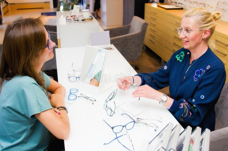 Πωλήτρια σαλονιών οπτικών με τον πελάτη της που επιλέγει eyeglasses στοκ εικόνα